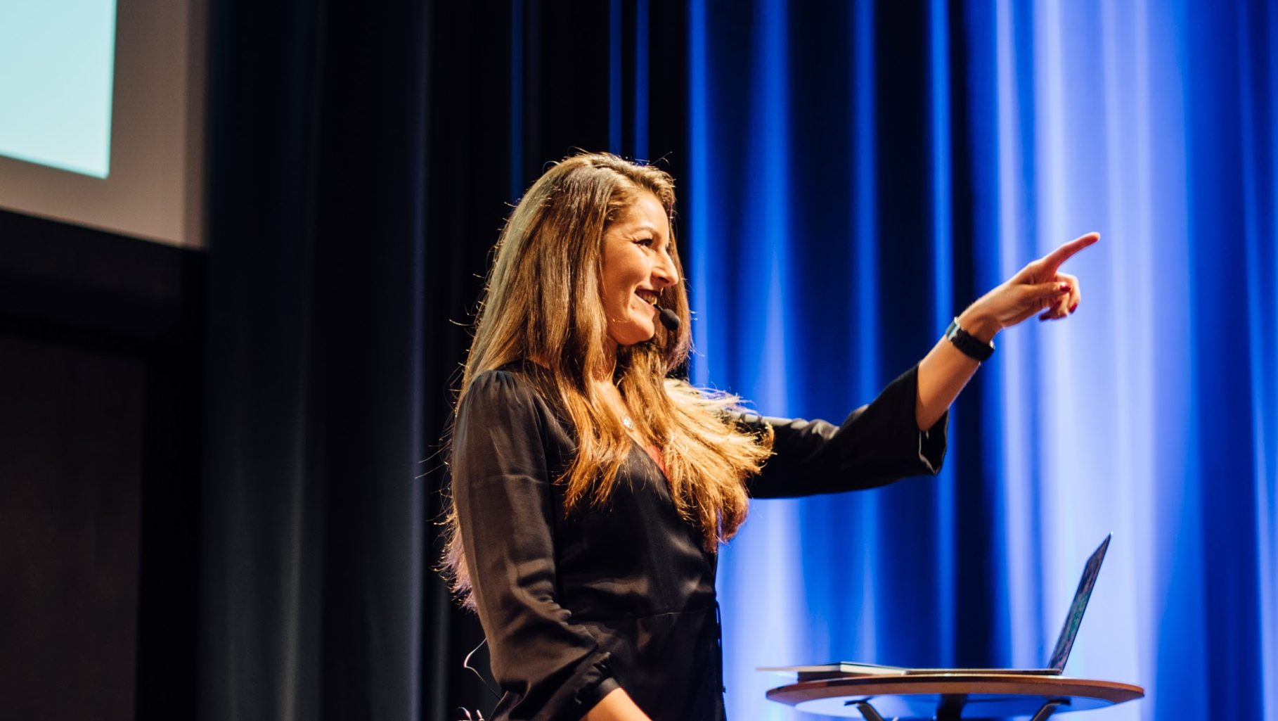 Female speaker on stage pointing and smiling