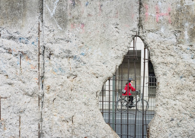 A hole in the Berlin wall with a cyclist visible through the hole